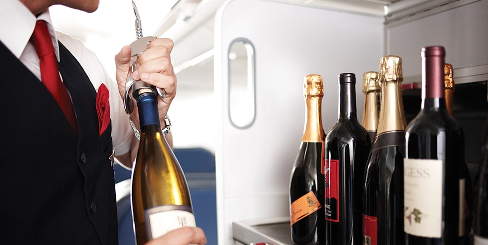 Flight attendant opening wine